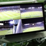 Referees re-check suspicious moments in a football game  via the monitor showing the recorded game.