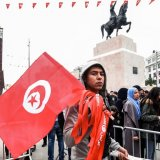 A Tunisian peddler selling national flag crosses a police roadblock on his way to a rally in the capital Tunis on Jan. 14.