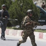 Afghan security personnel get into position at the site  of an attack on the Interior Ministry in Kabul on May 30.