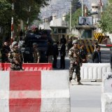 Afghan security forces stand guard near the site of a blast in Kabul on April 30.