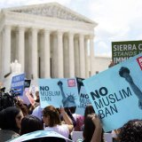 Protesters hold up signs and call out against the Supreme Court ruling upholding Trump's travel ban outside  the Supreme Court in Washington on June 26.
