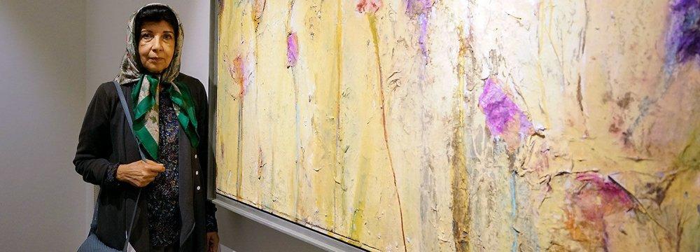 Shirin Ettehadieh standing next to one of her paintings