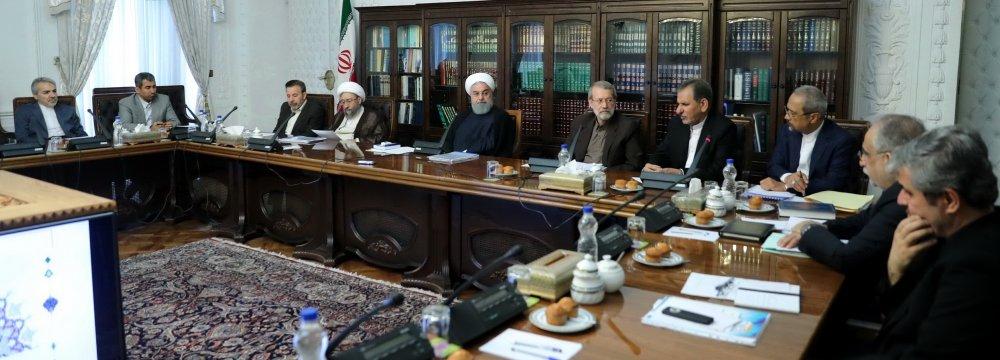 President Hassan Rouhani, flanked by Parliament Speaker Ali Larijani (R) and Judiciary Chief Ayatollah Sadeq Amoli Larijani, attended the meeting in Tehran on June 19.