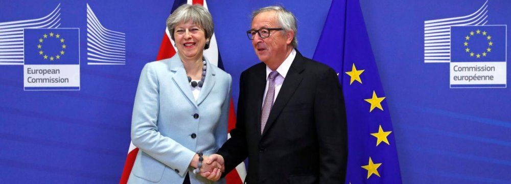 Prime Minister Theresa May is welcomed by European Commission President Jean-Claude Juncker in Belgium, December 8.