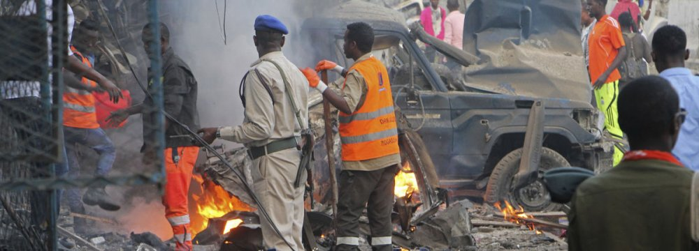 Somali soldier inspect wreckage of vehicles after a car bomb that was detonated in Mogadishu, Somalia, on Oct. 28.