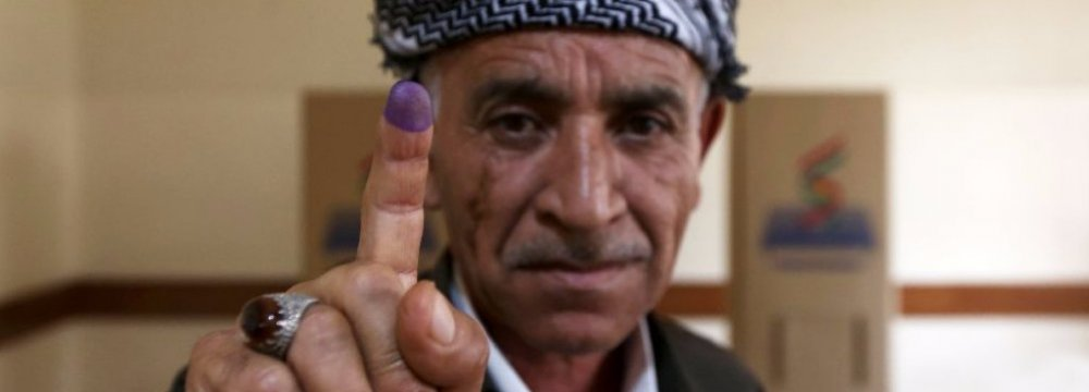 A Kurdish man shows his inked index finger after voting in an independence referendum in Erbil, Iraq on Sept. 25