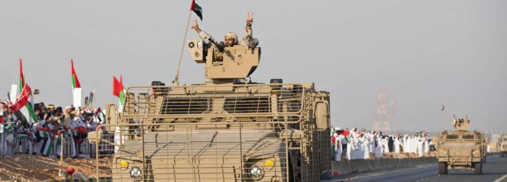 A member of the United Arab Emirates armed forces gestures to the crowd as the first batch of UAE military personnel returns from Yemen in Abu Dhabi, November 7, 2015.