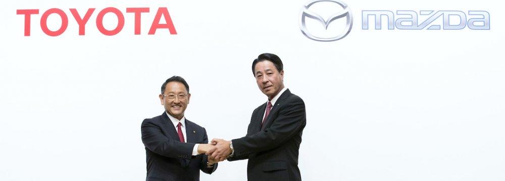 Toyota CEO Akio Toyoda (L) shakes hands with Mazda CEO Masamichi Kogai.