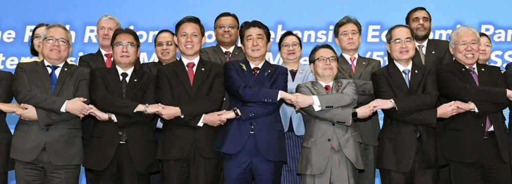 Japanese Prime Minister Shinzo Abe (C), joins hands with trade ministers from Asian countries for a group photo during the RCEP meeting in Tokyo on Sunday.