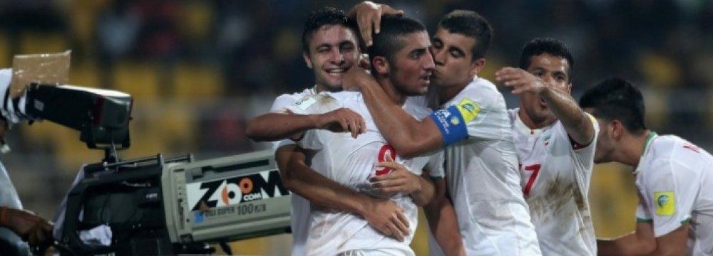 Iranian players rejoice after scoring a goal.