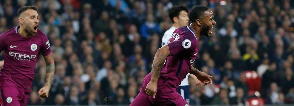 Manchester City's Raheem Sterling (R) celebrates scoring  his side's third goal against Tottenham Hotspur.