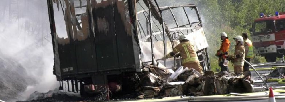 Firefighters at the site where a coach burst into flames after colliding with a lorry on a motorway near Muenchberg, Germany, in this still image taken from video on July 3.