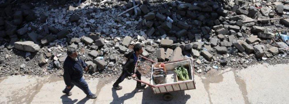 A man pushes a wheelbarrow next to debris in a street of Mosul, Iraq, on April 4.