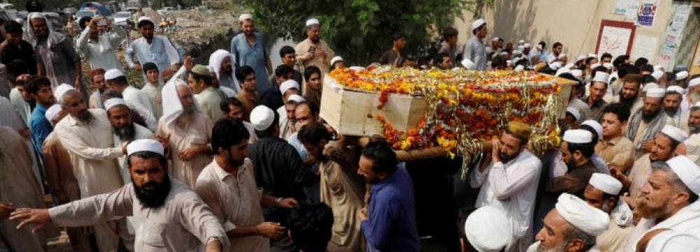 Men carry a coffin of a victim, who was killed with others in Tuesday's suicide attack in Peshawar, Pakistan, on July 11.