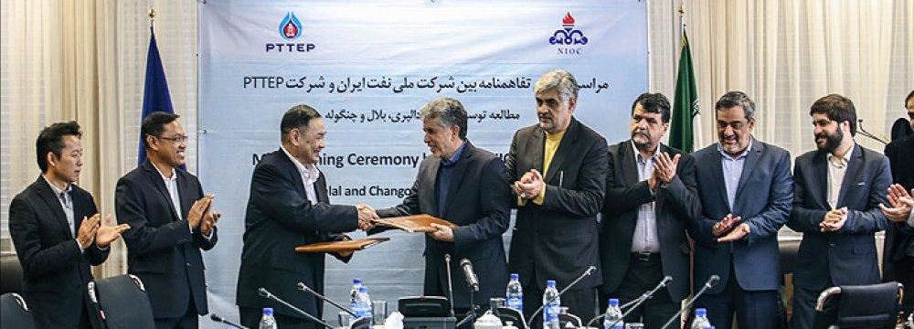 PTTEP Executive Vice President Prapat Soponpongpipat (3rd L) shakes hand with the NIOC deputy Gholamreza Manouchehri (4th L) in Tehran on Dec. 6.