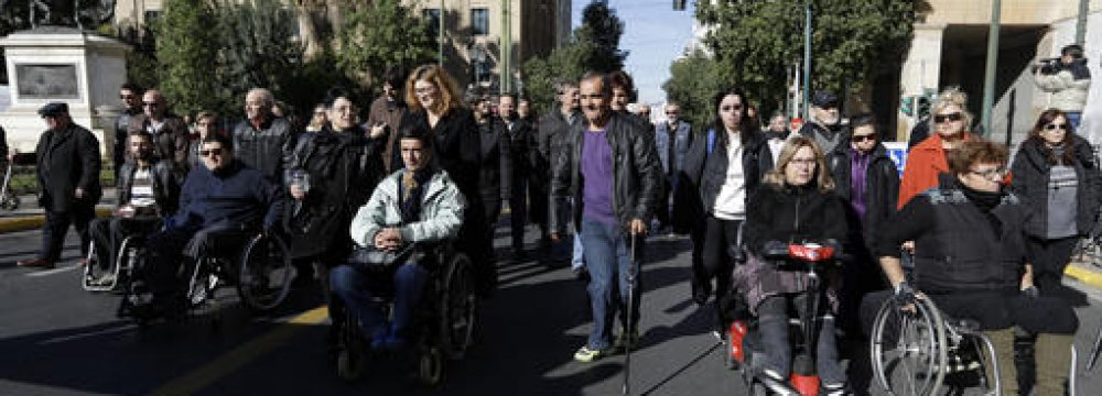 Disabled people with their families march during an  anti-government rally in central Athens on Friday, Dec. 2.