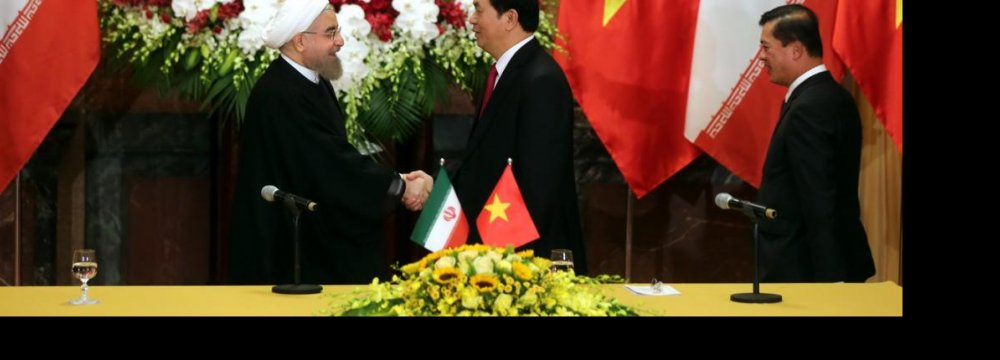 President Hassan Rouhani (L) shakes hands with Vietnamese President Tran Dai Quang in Hanoi, Vietnam, on Oct 6.