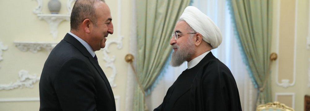 Turkish Foreign Minister Mevlut Cavusoglu (L) meets President Hassan Rouhani in Tehran on Nov. 26.