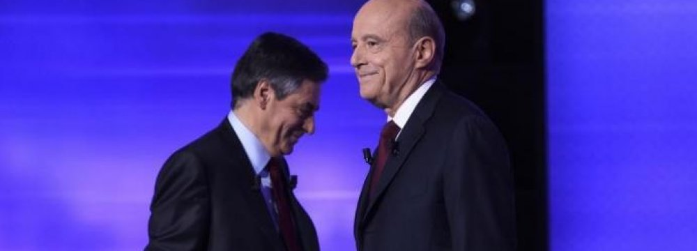 French politicians Alain Juppe (R) and Francois Fillon are seen on stage as they attend the third prime-time televised debate in Paris, November 24.