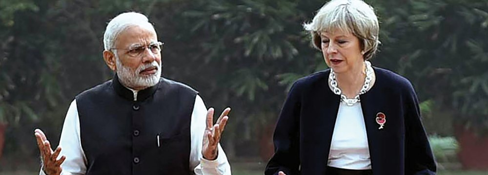 """Prime Minister Narendra Modi (L) walks with Britain's Prime Minister Theresa May at Hyderabad House in New Delhi. May described as """"limitless"""" the potential of the relationship with India."""