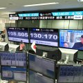A television screen (top R) displays file news footage of North Korean leader Kim Jong-Un, at a foreign exchange brokerage in Tokyo on August 29, after the North fired a missile over northern Japan.